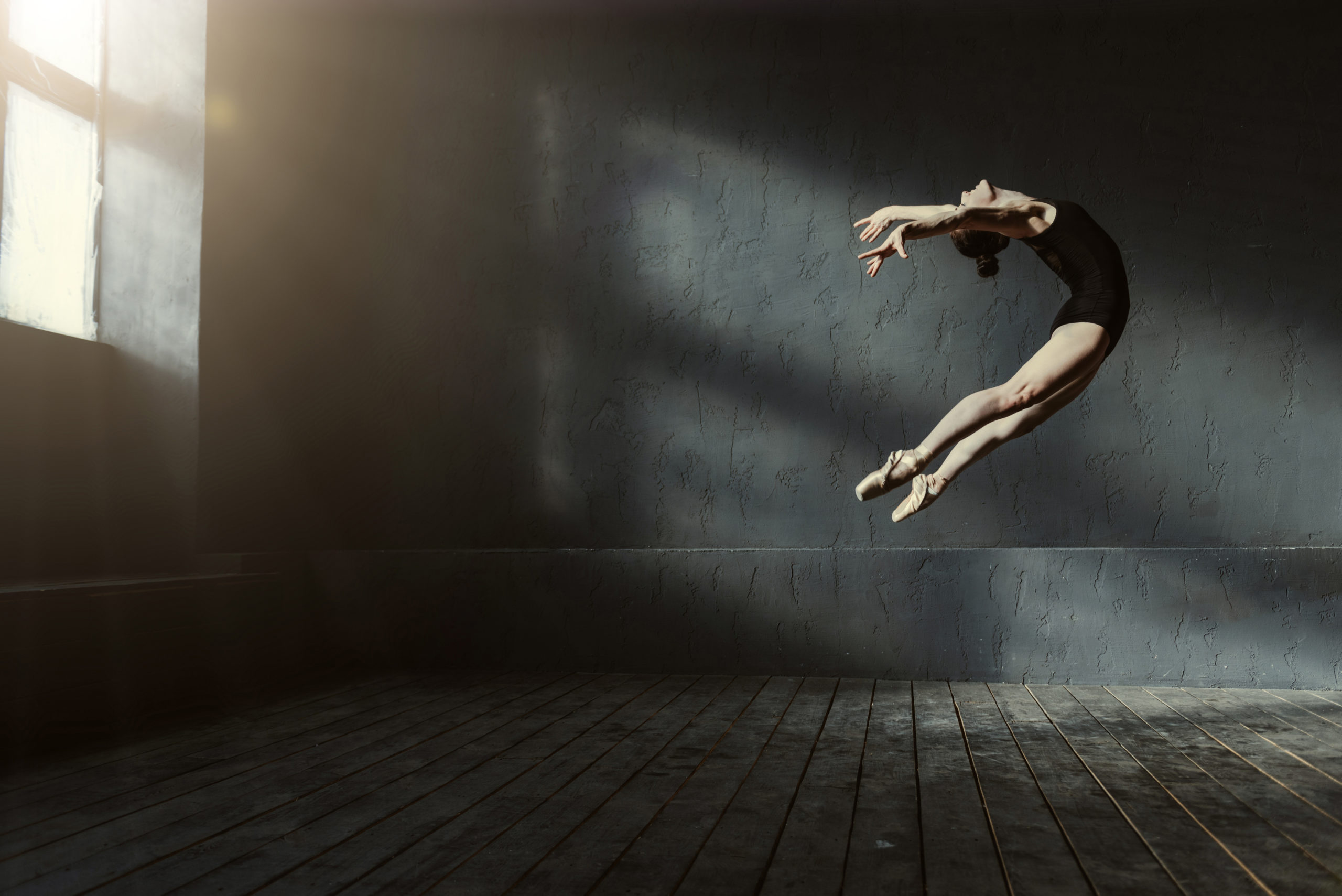 Performing jump in the air. Elegant graceful experienced ballet dancer demonstrating her flexibility and dancing in the black colored studio while standing on the tiptoes and looking above